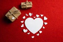 Liebesdekoration von den Weißbuchherzen umgeben durch großes Herz und zwei Präsentkartons auf rotem Hintergrund stockfotos