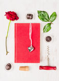 Liebesgeschichte, die mit Buch, Herzen, Rotrose, Schokolade und Korkenzieher auf weißem Hintergrund verfasst Stockfotografie
