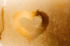 Liebesherzform und strukturiertes Muster der Regentropfen Abstraktes goldenes Farbfenster mit Wassertröpfchen, flüssige Blasen Ma Lizenzfreie Stockbilder
