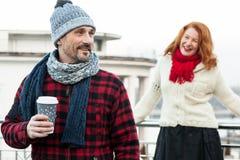 Liebeskaffee der glücklichen Paare Lächelnder Kerl hält Handwerksschale mit dem Kaffee, der sich hinten von der Freundin versteck Stockfotografie