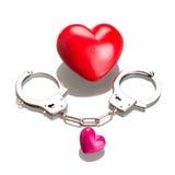 Liebessymbol in den Handschellen über Weiß Stockfotografie