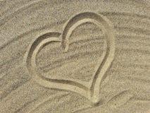 Liebessymbolabgehobener betrag auf dem Sand Lizenzfreie Stockbilder