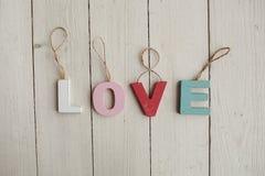 Liebesweinlesebuchstaben auf hölzernem Hintergrund Stockfotos
