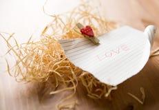 Liebeswort auf Blatt Papier Lizenzfreie Stockfotos