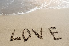 Liebeswort geschrieben auf den Sandstrand Stockbild