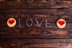 Liebeswort geschrieben mit Kreide und Plätzchen Stockbilder