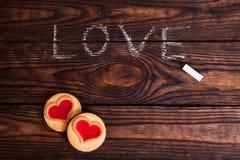 Liebeswort geschrieben mit Kreide und Plätzchen Stockbild