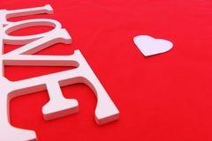 Liebeswort mit Herzen auf rotem Gewebe Stockbilder