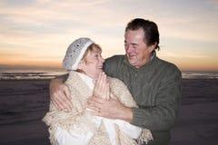 Liebevolle ältere Paare in den Strickjacken auf Strand Lizenzfreie Stockfotos