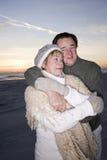Liebevolle ältere Paare in den Strickjacken auf Strand Lizenzfreie Stockbilder