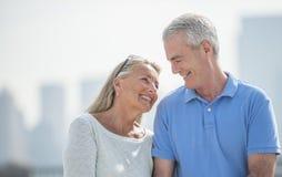 Liebevolle ältere Paare, die draußen lächeln Stockfotografie