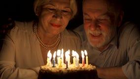 Liebevolle ältere Paare, die zu Hause Jahrestag mit Kuchen am Abend feiern Kerzen heraus durchbrennen stock footage