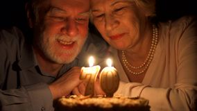Liebevolle ältere Paare, die zu Hause Jahrestag mit Kuchen am Abend feiern Kerzen heraus durchbrennen stock video