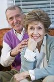 Liebevolle ältere Paare, die zusammen auf Couch sitzen Stockfoto