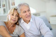 Liebevolle ältere Paare zu Hause, die auf Sofa sitzen Stockbild