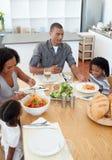 Liebevolle afrikanische Familie, die zusammen Teigwaren isst lizenzfreie stockfotografie