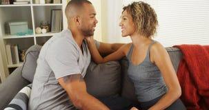 Liebevolle afrikanische Paare, die auf Couch sprechen Stockfotos