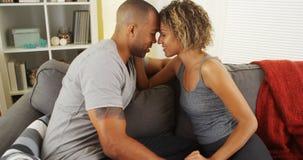 Liebevolle Afroamerikanerpaare, die auf Couch sprechen Stockfotos