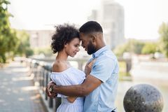 Liebevolle Afroamerikanerpaare, die auf der Brücke umarmen stockfotos