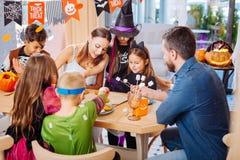 Liebevolle Eltern, die ihre Kinder tragen Halloween-Kostüme mit Bonbons behandeln stockfotografie