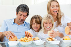 Liebevolle Familie, die Hamburger isst lizenzfreies stockbild
