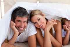 Liebevolle Familie, die Spaß mit auf Bett hat Lizenzfreie Stockbilder