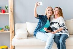 Liebevolle Familie unter Verwendung des Smartphone für das Fotografieren Stockfotos