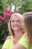 Liebevolle jugendliche Tochter, die ihre lächelnde Mutter küsst lizenzfreie stockbilder