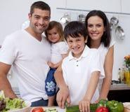 Liebevolle junge Familie, die zusammen kocht Stockfotos