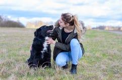 Liebevolle junge Frau mit ihrem loyalen schwarzen Hund Stockbilder