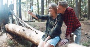 Liebevolle junge kaukasische Paare, die Selbstporträt in einem Wald nehmen Lizenzfreies Stockfoto