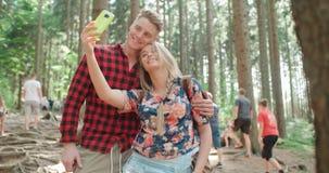 Liebevolle junge kaukasische Paare, die Selbstporträt in einem Wald nehmen Stockfotos