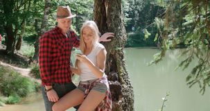 Liebevolle junge kaukasische Paare unter Verwendung des Telefons durch einen See Lizenzfreie Stockfotos