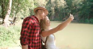 Liebevolle junge kaukasische Paare unter Verwendung des Telefons durch einen See Stockfotografie