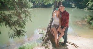 Liebevolle junge kaukasische Paare unter Verwendung des Telefons durch einen See Stockfoto