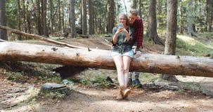 Liebevolle junge kaukasische Paare unter Verwendung des Telefons in einem Wald Stockbild