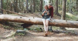 Liebevolle junge kaukasische Paare unter Verwendung des Telefons in einem Wald stock video footage