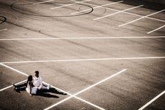 Liebevolle junge Paare an der Hochzeit auf einem leeren Autoparking Lizenzfreie Stockfotografie