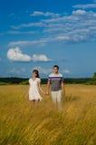 Liebevolle junge Paare, die auf dem Gebiet gehen stockbild