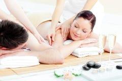 Liebevolle junge Paare, die eine rückseitige Massage genießen Stockfoto