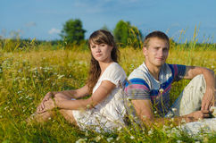 Liebevolle junge Paare, die im Sonnenlicht sitzen lizenzfreie stockbilder