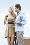 Liebevolle junge Paare, die Rotwein Restaurant am im Freien durch See essen Stockfotos