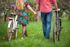 Liebevolle junge Paare mit Fahrrädern stockfotos