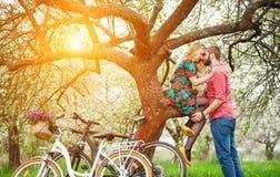 Liebevolle junge Paare mit Garten der Fahrräder im Frühjahr Lizenzfreies Stockfoto