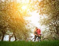 Liebevolle junge Paare mit Garten der Fahrräder im Frühjahr Stockfotografie