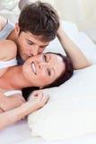 Liebevolle kaukasische Paare, die zu Hause auf Bett liegen Stockfotografie