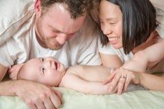 Liebevolle Mischrasse chinesisch und kaukasisches Baby, das in Bett mit seinem legt stockfoto