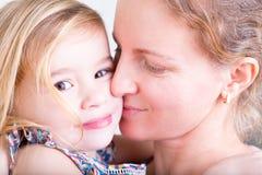 Liebevolle Mutter, die ihre kleine Tochter küsst Stockfotografie