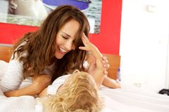 Liebevolle Mutter, die mit Tochter auf Bett spielt Lizenzfreie Stockfotos
