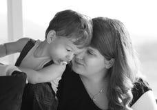 Liebevolle Mutter und Sohn der Nahaufnahme, die Geheimnisse in Ohren flüstert Stockfoto